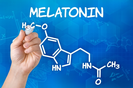 scientist: Hand with pen drawing the chemical formula of melatonin