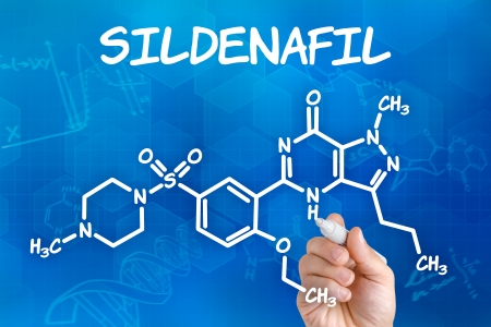 erectile dysfunction: Hand with pen drawing the chemical formula of sildenafil Stock Photo