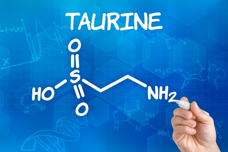 Hand with pen drawing the chemical formula of taurine photo