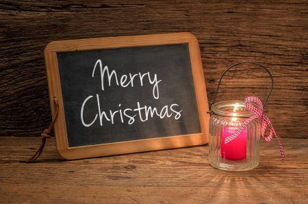 Candle in front of a chalkboard with the text Merry Christmas photo
