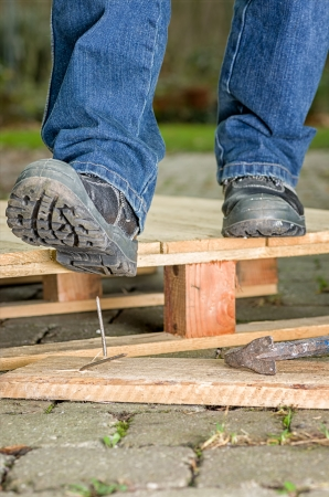 work safe: Worker with safety boots steps on a nail Stock Photo