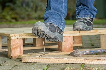 the sole of the shoe: Worker with safety boots steps on a nail Stock Photo