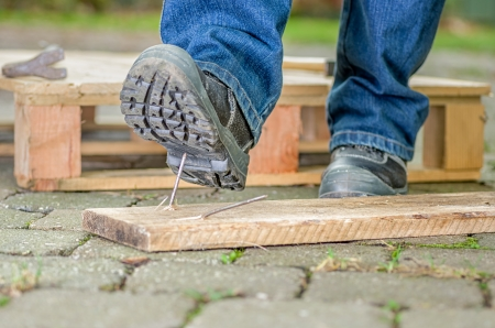 work boots: Worker with safety boots steps on a nail Stock Photo