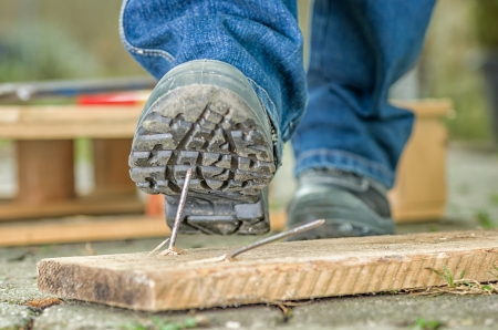 foot gear: Worker with safety boots steps on a nail Stock Photo