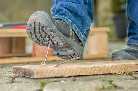 construction nails: Worker with safety boots steps on a nail Stock Photo