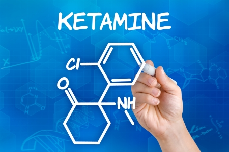 antidepressant: Hand with pen drawing the chemical formula of ketamine