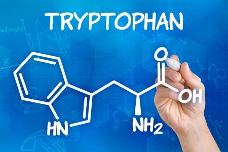 supplement: Hand with pen drawing the chemical formula of tryptophan