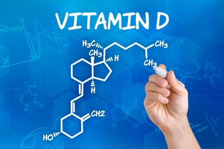 Mano con el dibujo de la fórmula química de la vitamina d pluma Foto de archivo