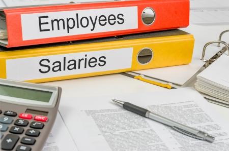 salarios: Carpetas con los empleados y los sueldos de la etiqueta Foto de archivo