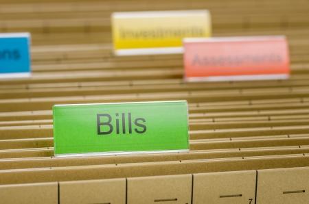 debt management: Hanging file folder labeled with Bills