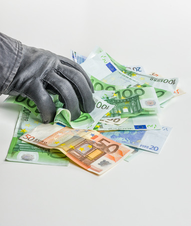Thief with leather glove is grabbing some bills photo