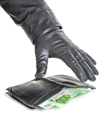 Thief with leather glove is reaching for a wallet photo