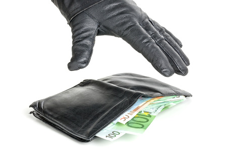 Thief with leather glove is reaching for a wallet Stock Photo