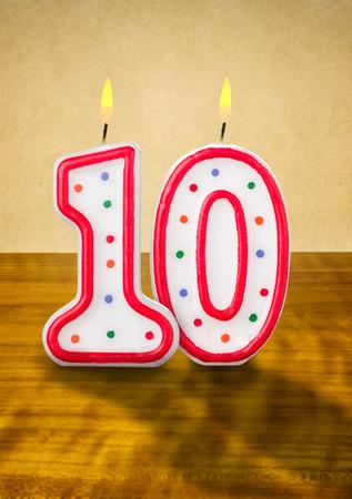 La quema de velas en su cumpleaños número 10 Foto de archivo - 26147016