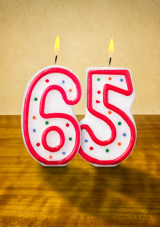 65th: Burning birthday candles number 65 Stock Photo