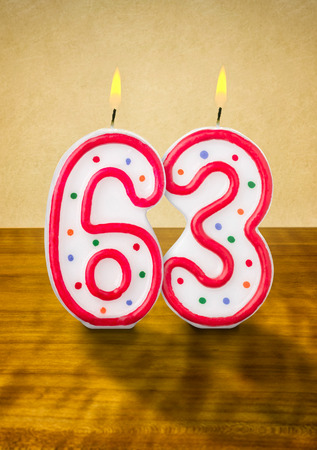 third age: Burning birthday candles number 63 Stock Photo