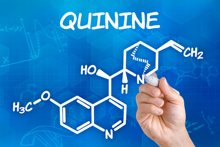 quinine: Hand with pen drawing the chemical formula of quinine