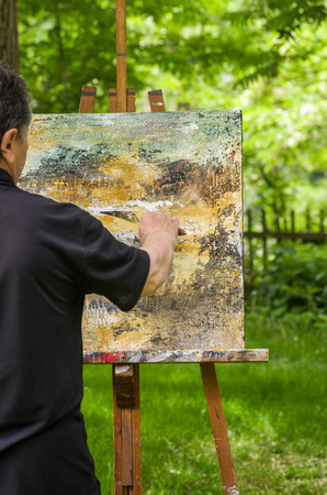hombre pintando: Artista pinta un cuadro abstracto Foto de archivo