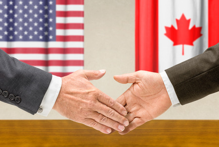 foreign policy: Representatives of the USA and Canada shake hands Stock Photo