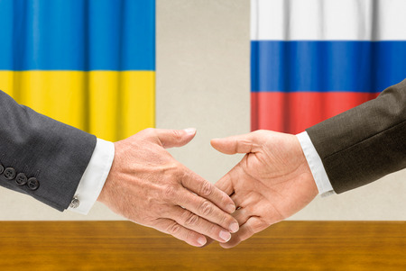 Representatives of  Ukraine and Russia shake hands photo