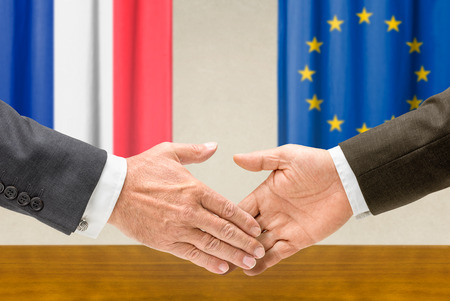 Representatives of France and the EU shake hands photo