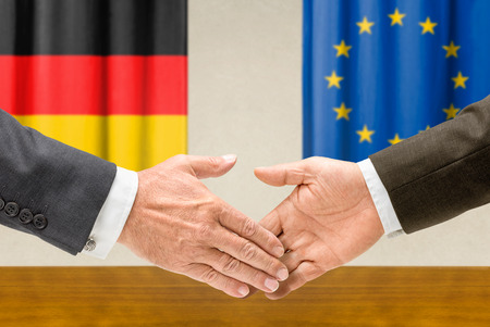 Representatives of Germany and the EU shake hands photo