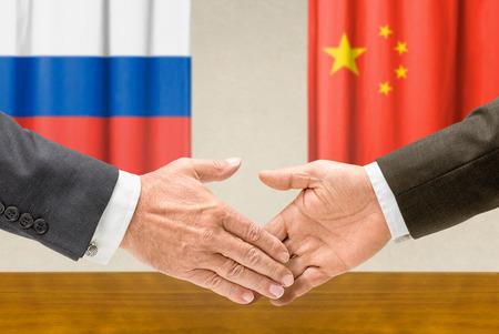 china flag: Representatives of Russia and China shake hands