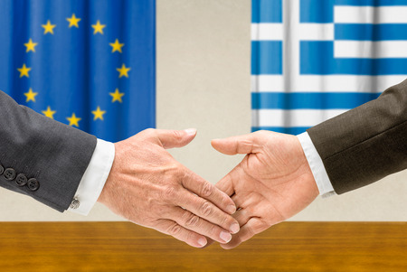 Representatives of the EU and Greece shake hands photo
