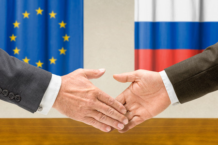 Representatives of the EU and Russia shake hands photo