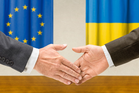 Representatives of the EU and Ukraine shake hands photo