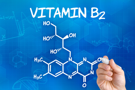 Hand with pen drawing the chemical formula of  Vitamin B2 photo
