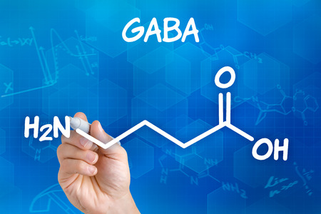 Hand with pen drawing the chemical formula of GABA Reklamní fotografie