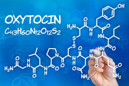 fidelidad: Mano con el dibujo de la fórmula química de la oxitocina pluma Foto de archivo