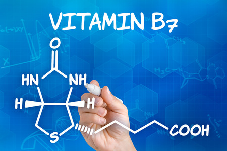 biotin: Hand with pen drawing the chemical formula of Vitamin B7