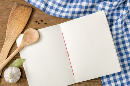 Book with wooden spoons on a blue checkered tablecloth photo