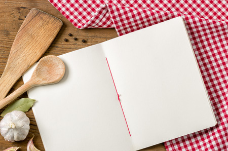 Book with wooden spoons on a red checkered tablecloth photo