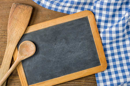Chalkboard with wooden spoons on a blue checkered tablecloth photo