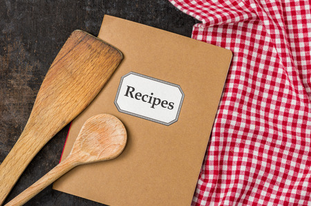 Recipe book with wooden spoons on a red checkered tablecloth photo