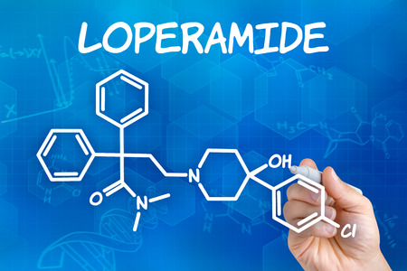 opioid: Hand with pen drawing the chemical formula of Loperamide