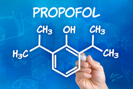 anaesthesia: Hand with pen drawing the chemical formula of Propofol Stock Photo