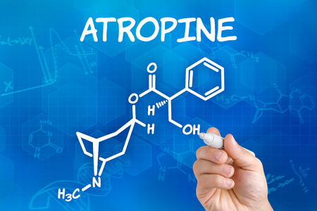acetylcholine: Hand with pen drawing the chemical formula of Atropine Stock Photo