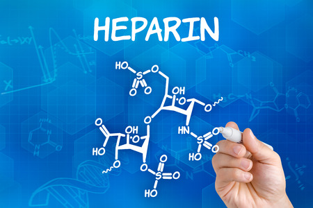 anticoagulant: Hand with pen drawing the chemical formula of Heparin