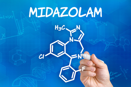 benzodiazepine: Hand with pen drawing the chemical formula of Midazolam Stock Photo