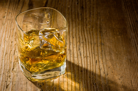 Whiskey on the rocks on a wooden background photo