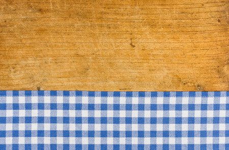 Rustic wooden background with a blue checkered tablecloth photo