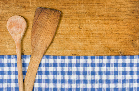 menue: Wooden background with a blue checkered tablecloth and wooden spoon Stock Photo