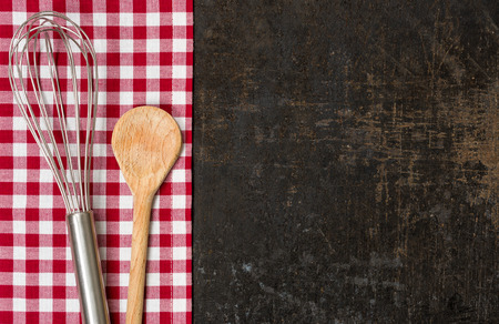 menue: Old baking tray with red checkered table cloth and baking utensils Stock Photo