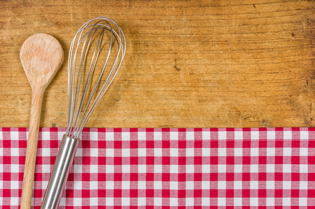 Wooden background with whisk and wooden spoon photo
