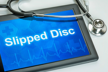 spinal disc herniation: Tablet with the text Slipped disc on the display Stock Photo