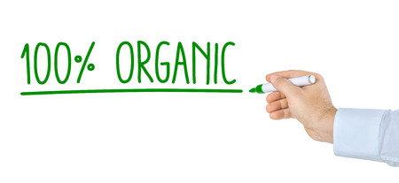 eco slogan: Hand with pen writing 100 percent organic